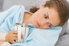 有有的流感的生气的少妇杯子热的饮料 图库摄影