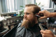 有有胡子的人与头发剪刀的理发 免版税库存图片