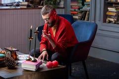 有有胡子的占卜者有些困难,当在家时工作 免版税库存图片