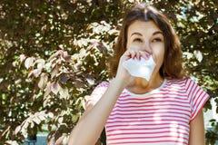 有有过敏症状吹的鼻子的妇女在公园 免版税库存照片