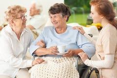 有朋友和护士的微笑的被麻痹的资深妇女 库存照片