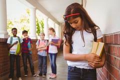 有朋友的哀伤的女小学生在学校走廊的背景中 免版税库存照片
