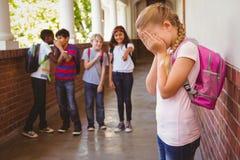 有朋友的哀伤的女小学生在学校走廊的背景中 库存图片