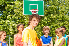 有朋友的微笑的男孩后边在篮球期间 免版税库存照片