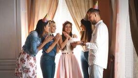 有朋友的生日快乐女孩做一个愿望并且吹灭在蛋糕的蜡烛 股票录像