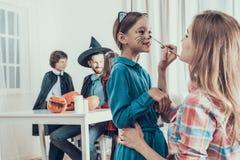 有服装的母亲帮助的女儿为万圣节 免版税库存图片