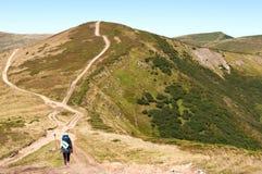 有朝向对山小山的背包的一个女孩 免版税库存图片