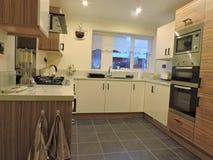 有木作用和黑辅助部件的奶油色厨房 库存图片