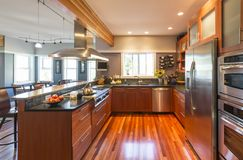 有木内阁、硬木地板、不锈钢装置、窗口和口音照明设备的优质当代家庭厨房 免版税库存图片