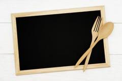 有木匙子的空白的在白色木板条背景的黑板和叉子 免版税图库摄影