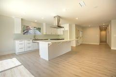有木地板和宽敞现代厨房的空的家 免版税库存图片
