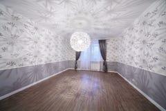 有木地板和异常的枝形吊灯的宽敞轻的室 免版税库存图片