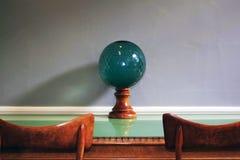 有木基地的绿色玻璃碗在一张绿色玻璃桌和两把椅子顶部 免版税图库摄影
