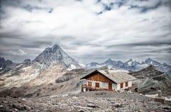 有木屋顶的冬天房子在一个多山风景里面 免版税库存照片