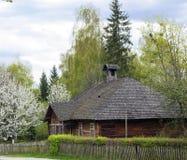 有木屋顶的老木房子在开花树附近的村庄 图库摄影