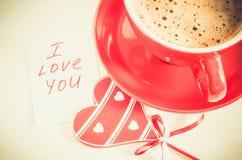 有木心脏和笔记的热奶咖啡杯子我爱你 免版税图库摄影