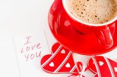 有木心脏和笔记的热奶咖啡杯子我爱你 库存照片