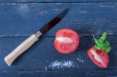 有木把柄和一把黑刀片的刀子 切的蕃茄 图库摄影