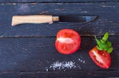 有木把柄和一把黑刀片的刀子 在黑背景的切的红色蕃茄 库存照片