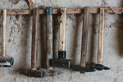 有木把柄和减速火箭的葡萄酒肮脏的样式金属技巧的锤子工具,垂悬在钉子反对一个网的背景与 免版税库存图片