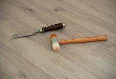 有木把柄和特别锤子的金属凿子在层压制品的背景 免版税库存照片