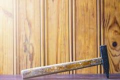 有木把柄的一把锤子在委员会背景  免版税库存图片