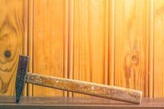 有木把柄的一把锤子在委员会背景  图库摄影