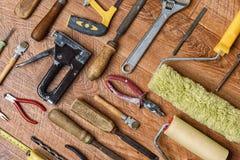 有木把柄的不同的工具为修理:钳子,玻璃刀,凿子,在木背景的台板 免版税图库摄影