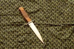 有木把柄的匕首以绿色keffiyeh为背景 免版税库存照片