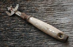 有木把柄的生锈的开罐头用具 免版税库存图片