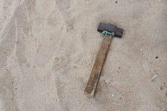 有木把柄的老锤子在沙子海滩背景 库存图片