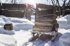 有木柴的老木爬犁在一条积雪的道路站立 库存图片