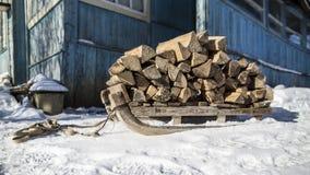 有木柴的老木爬犁在一条积雪的道路站立 库存照片