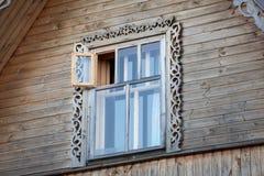 有木框架窗口的木房子在屋顶土坎 库存图片