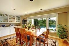 有木桌集合、白色内阁和绿色墙壁的明亮的餐厅 库存照片