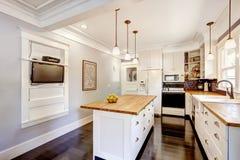 有木桌面海岛和电视的白色厨房 免版税库存照片