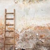 有木梯子的被风化的灰泥墙壁 库存图片