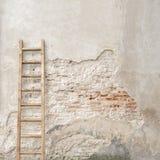 有木梯子的被风化的灰泥墙壁 库存照片