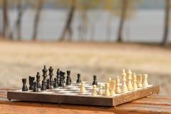 有木棋子的棋盘在长木凳 库存照片