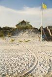 有木楼梯、黄旗和轮胎踩的海滨别墅在沙子 免版税库存照片