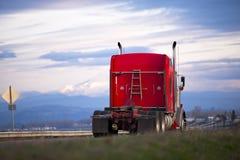 有木楼梯的红色经典半卡车在风景路 图库摄影
