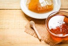 有木浸染工的新鲜的甜蜂蜜在白色板材的瓶子和蜂窝在木桌背景 免版税库存照片