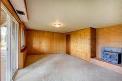 有木盘区墙壁和生铁壁炉的空的客厅 免版税图库摄影