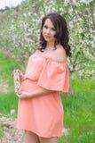 有木砖的怀孕的女孩在庭院里 免版税库存图片