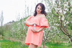有木砖的怀孕的女孩在庭院里 免版税库存照片