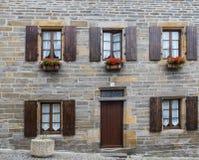 有木窗口系列的典型的石建筑与fl的 免版税库存图片