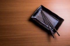 有木筷子的日本式板材在木背景 免版税库存照片