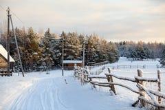 有木篱芭的农村多雪的被盖的路在冬天季节的俄国村庄 俄国 库存图片