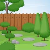 有木篱芭的绿色庭院 与各种各样的植物的家庭菜园 免版税库存图片