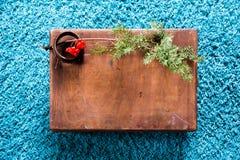 有木纹理的箱子和在蓬松蓝色地毯背景的杉树 顶视图拷贝空间 免版税库存照片